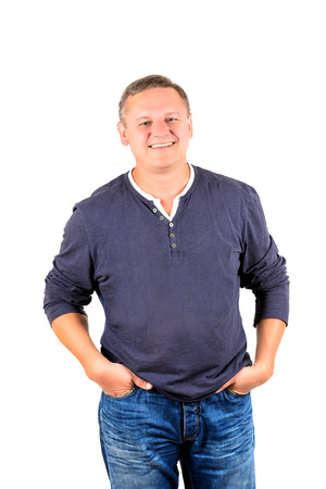 Casually dressed middle aged man smiling. 3/4 view of man shot in vertical format isolated on white.