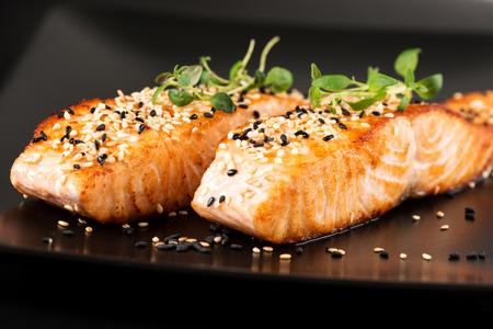 Grilled salmon, sesame seeds  and marjoram on a black plate. Studio shot