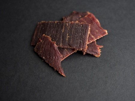 Beef jerky in pieces isolated on black background