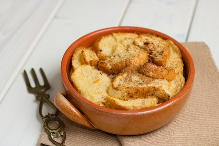 Bread pudding in earthenware pot with rustic brass fork