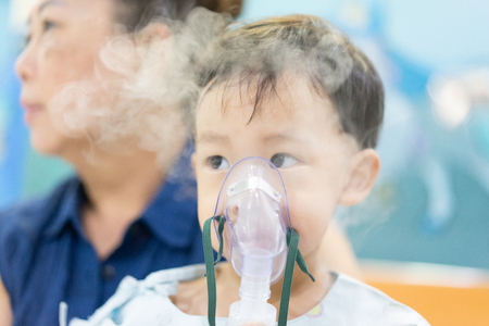 Photo pour Grandmother tack care a moody boy who is sick with a chest infection after a cold or flu has difficulty breathing and cough for a long time. Therefore, a doctor giving medicine with a mask. - image libre de droit
