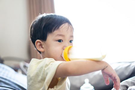Photo for A boy is sucking a bottle of milk in the morning while watching TV in the bed in the bedroom. - Royalty Free Image