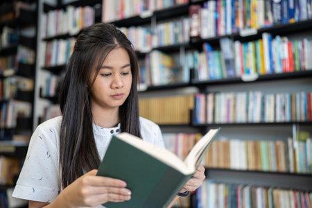 Photo pour Asian woman is reading a book in the university library. - image libre de droit