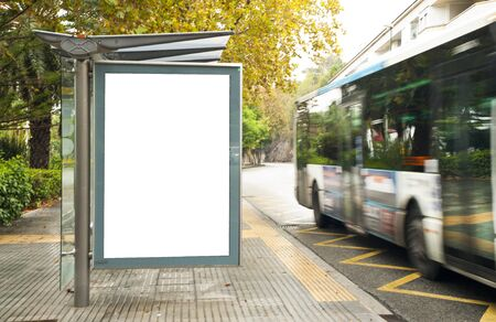 Photo pour White blank vertical billboard at the bus stop on the city street. In the background of buses and roads. Sketch. Poster on the street next to the road. - image libre de droit