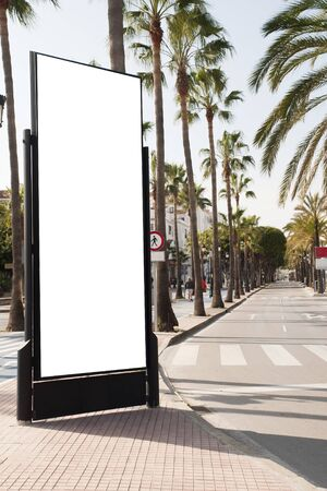 Photo pour Billboard, banner, empty, white in the city center with palm trees, green plants - image libre de droit