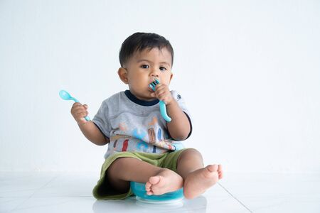 Photo for Cute little asin baby boy with spoon - Royalty Free Image