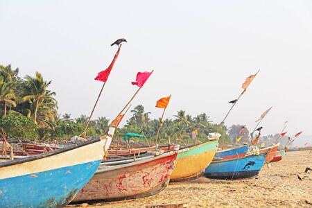 Photo pour Bright fishing boats stand on the sand in India, GOA. Multicolored Indian boat on the background of the sea. A crow or a bird sits on top of the boat. - image libre de droit