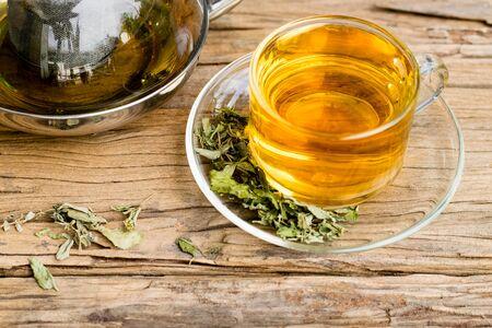 Foto de Stevia tea in a glass cup with Dry stevia leaves on an old wood background. - Imagen libre de derechos
