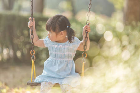 Photo pour Little girl having to play swing first time in the playground , the evening - image libre de droit