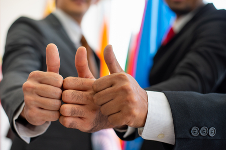 Photo pour Three of thumbs up from business man or politician during international conference - image libre de droit