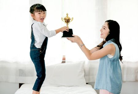 Photo for Asian daughter express exciting after get reward as trophy from her mother and she stand on white bed. - Royalty Free Image