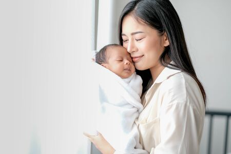 Photo pour White shirt Asian mother is kissing her newborn baby in bedroom in front of glass windows with white curtain to show love and family bonding. - image libre de droit