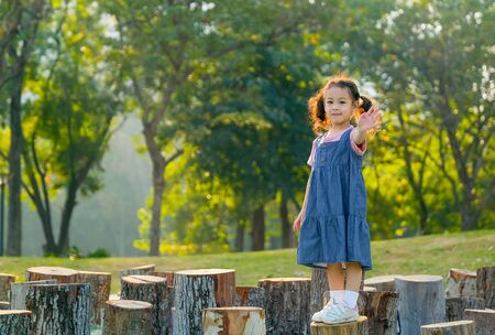 Photo pour Young asian little girl stand on timber and also wave her hand with morning light in the garden. - image libre de droit