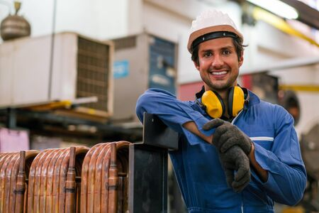 Photo pour Factory worker man stand near copper tube or pipe and smiling in workplace look happy. Concept of good management system for industrial business. - image libre de droit