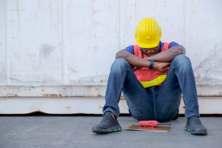 Photo for American African engineer or factory worker man sit close to cargo container and he look tire and also sleepy or lost job. Concept of good system and manager support for better industrial business. - Royalty Free Image