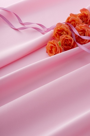 red roses and ribbon on the pink satinの写真素材