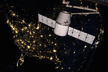 Photo pour SpaceX Dragon orbiting the planet Earth. - image libre de droit