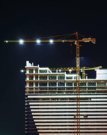 Photo pour Empty illuminated construction site and yellow crane at night - image libre de droit