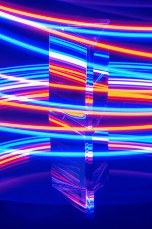 Photo for A glass prism with reflection on a abstract blue neon colorful stripey background - Royalty Free Image