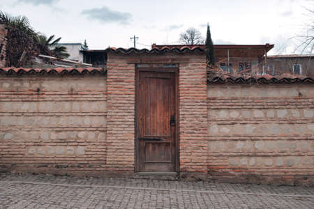 Photo pour Wooden door with a round metal handle in the fence made with rocks and bricks - image libre de droit
