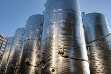 Photo pour Stainless tanks for processing and fermentation wine production in the open air with blue sky background. Modern wine factory - image libre de droit
