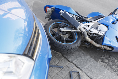 Photo pour The accident blue bike with a blue car. The motorcycle crashed into the bumper of the car on the road. The motorcycle lies on the road near the car. - image libre de droit