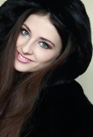 Beautiful smiling woman in fur hood coat looking happy  Closeup portrait