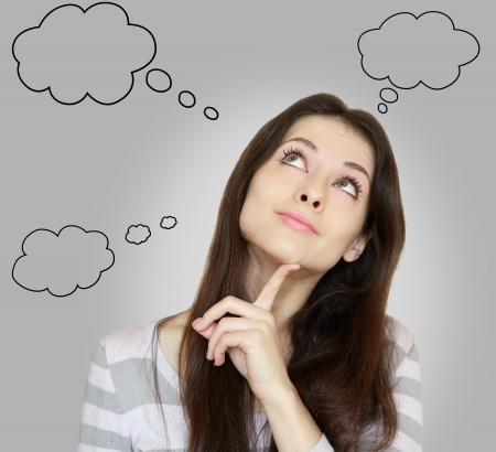 Thinking woman with many ideas in empty bubble on grey background looking up with finger at face