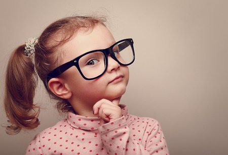 Photo pour Thinking kid girl in glasses looking happy - image libre de droit