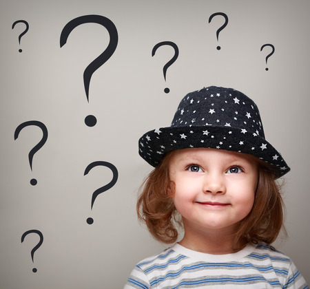 Photo pour Happy thinking kid girl in hat looking up on many questions above the head - image libre de droit