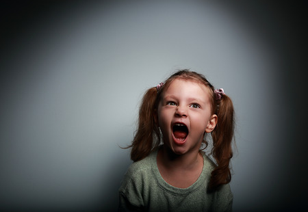 Angry child girl screaming with opened mouth and looking up with evil on dark background