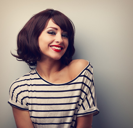 Happy laughing young woman with short hair in fashion blouse. Vintage closeup portraitの写真素材