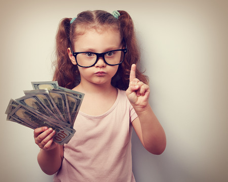 Cute kid girl holding dollars and have an idea how earning much money in crisis. Serious child teaching in eyeglasses. Vintage closeup portrait