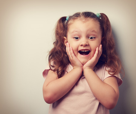 Happy very excited kid girl with open mouth looking. Closeup vintage portrait