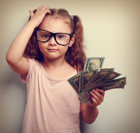 Small professor in eye glasses scratching head, holding money and thinking how earring more. Kid have an big idea. Emotional closeup vintage portrait