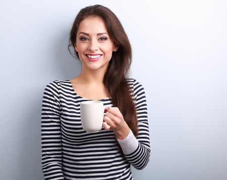 Happy toothy smiling casual young woman with cup of tea on blue background with empty copy space