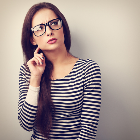 Annoyed angry young woman in eyeglasses thinking and looking up. Vintage closeup portraitの写真素材