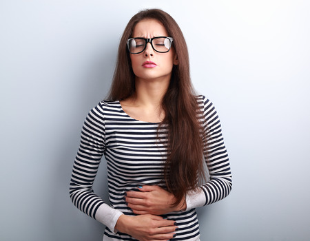 Beautiful stressed business woman in eyeglasses suffering from pain in stomach on blue background