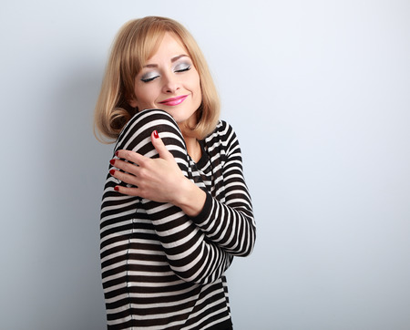 Happy makeup blond woman hugging herself with natural emotion on enjoying face with close eyes. Love concept by yourself