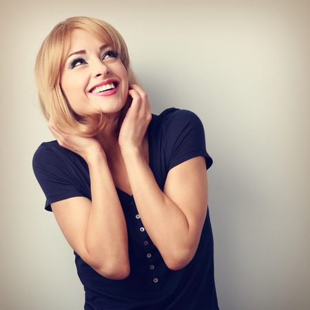 Photo pour Happy laughing young woman with blond hair style looking up. Toned portrait - image libre de droit