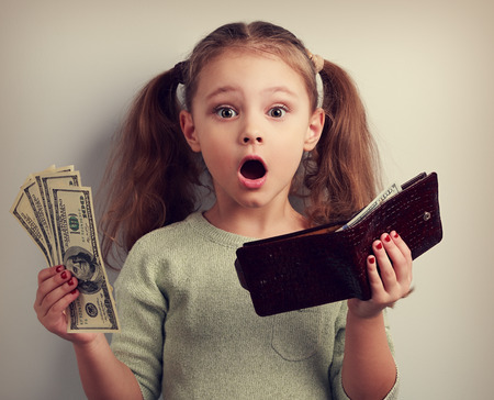 Foto de Cute surprising kid girl holding wallet and dollars with open mouth and think how can to spend so much money. Happy childhood. Toned closeup portrait - Imagen libre de derechos