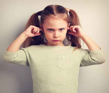 Photo for Angry unhappy kid girl coverd ears the fingers and gesturing that not want to listen. Vintage toned portrait - Royalty Free Image