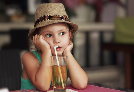 Cute kid girl in hat drinking apple juice in cafe and thinking about life with serious face