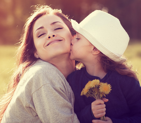 Photo pour Happy daughter kissing her enjoying mother on summer sunny background - image libre de droit