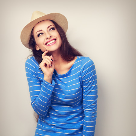 Photo pour Happy laughing woman in straw hat thinking and looking up empty copy space. Toned portrait - image libre de droit