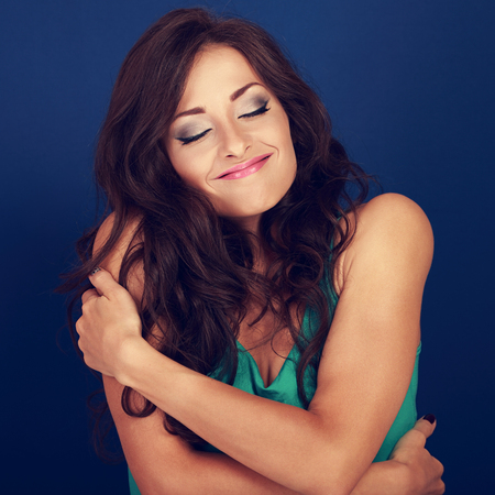 Happy makeup woman hugging herself with natural emotional enjoying face. Love concept of yourself body and face on blue background. Closeup
