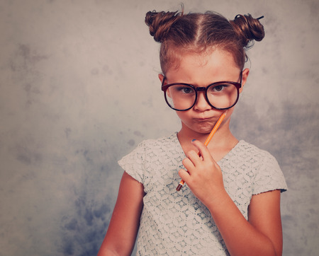 Serious strict kid girl in eye glasses holding pencil and thinking about with trendy hair style on blue background. Toned closeup portrait