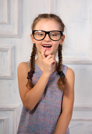 Excited positive thinking kid girl in fashion glasses with emotional natural smiling face looking on studio background. Closeup portrait