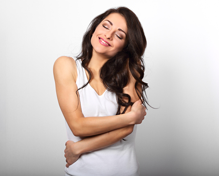 Foto de Happy sporty woman hugging herself with natural emotional enjoying face on white background. Love concept of yourself body - Imagen libre de derechos