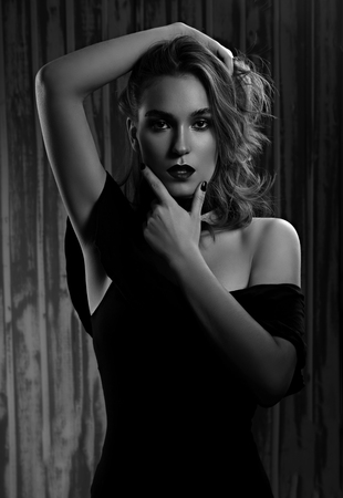 Photo pour Mystic sexy makeup woman holding the hand long curly hairstyle and looking passion on dark shadow background. Art portrait. Black and white - image libre de droit
